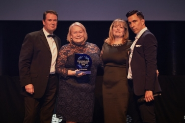 Susan Peary, managing director and Helen Lupton, compliance director receiving their award, from comedian Russell Kane, at the IIP Awards Ceremony